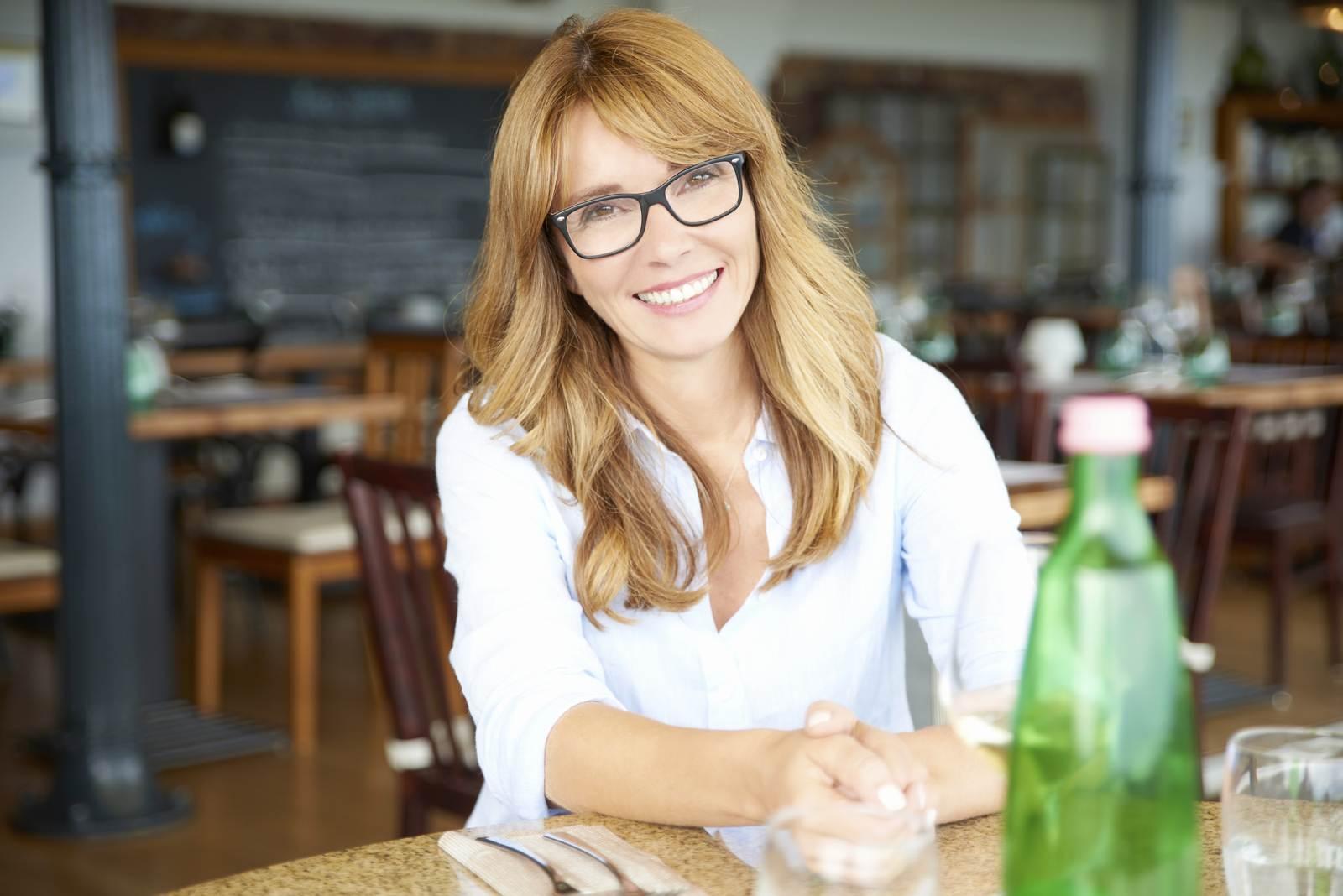 donna matura al tavolo beve acqua