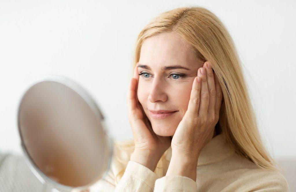 donna allo specchio si guarda le rughe